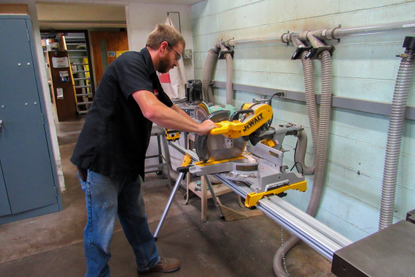 Kody Habeck using a saw at the machine shop