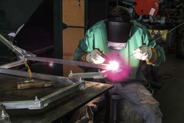A student welding at the machine shop